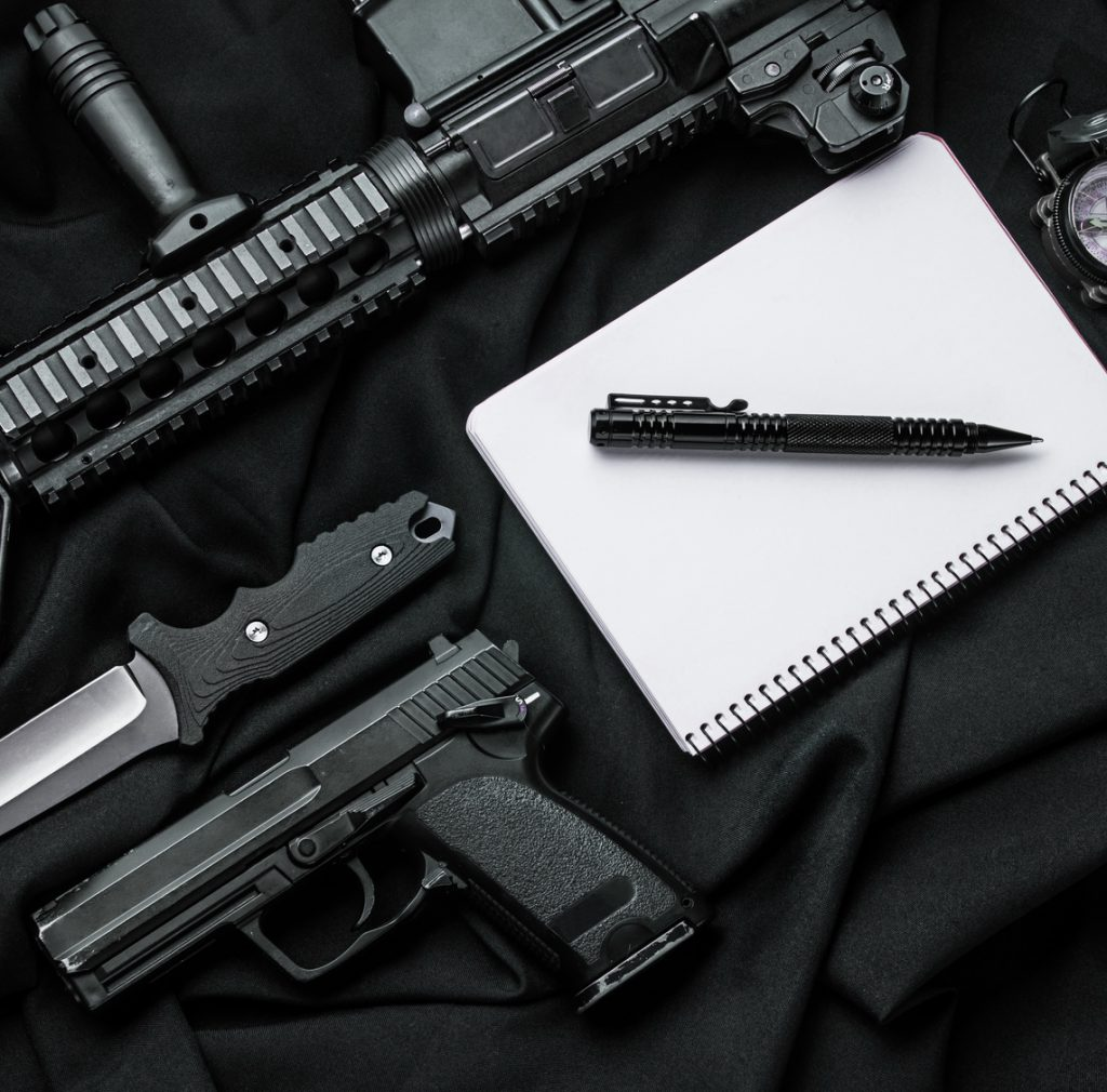 Кifle, pistol,  knife,  notebook with  pen and compass lying on black cloth. Top view
